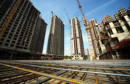 Photo for Between tall buildings under construction and cranes under a blue sky - Royalty Free Image