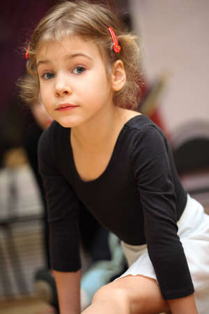 little girl in ballet class sits on string on floor and looks into camera