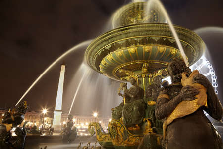 Luxor obelisk and Fontaine des Mers at the Place de la Concorde in the evening.
