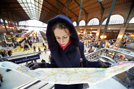 PARIS - DECEMBER 31: Young woman explores the map of Paris on the second floor of the station Gare de Est, December 31, 2009, Paris, France. Gare de Est - Eastern Railway Station of Paris, one of six large Parisian railway stations of the National Company