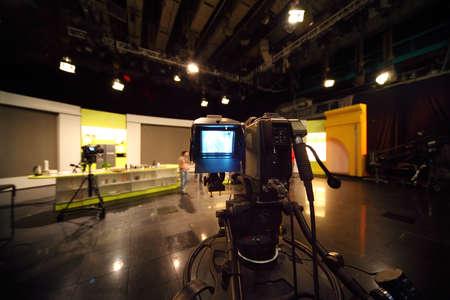 professional black video camera in television studio, light scene