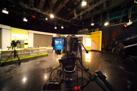 professional black video camera in television studio, light scene