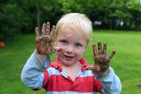 Young boy shows his muddy hands