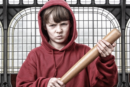 Young aggresive teenage boy with a baseball bat