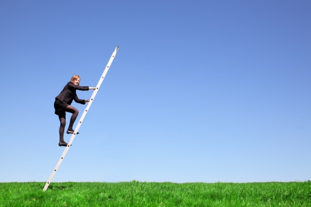 Young businesswoman climbs a ladder on green meadow and blue sky