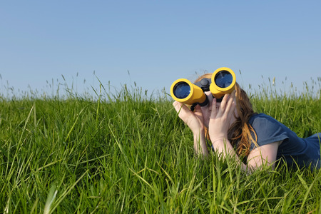 Young girl with binoculars in a meadow searching the sky