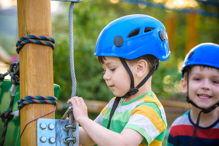 Happy children having fun in adventure park. Two adventurous healthy preschool boys, twin brothers enjoying active day outdoors climbing on the trees. Friendship and brotherhood concept.