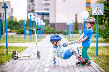 Foto de Two boys sibling brothers together in park, helps boy with roller skates to stand up after fall. Friendship and active leisure summer holidays time with family concept. - Imagen libre de derechos