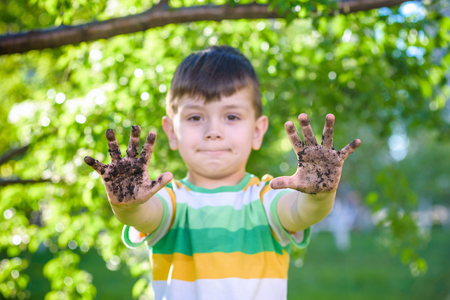 Foto de A young Caucasian boy showing off his dirty hands after playing in dirt and sand outdoors sunny spring or summer evening on blossom trees background. happy childhood friendship concept. - Imagen libre de derechos