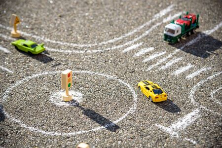 Photo pour Toy cars red green blue color on the road chalked on black asphalt. Difficult traffic rules concept. - image libre de droit