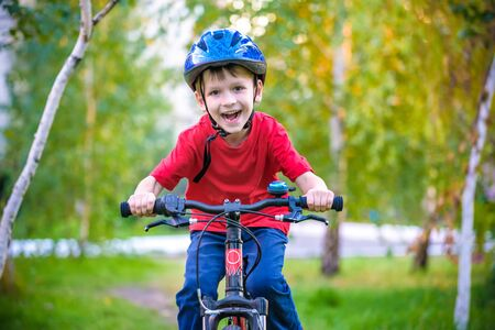 Photo pour A small white Toddler boy in a protective helmet on his head sits on a children's bicycle. Toddler on a two-wheeled red bicycle looks forward. A sly smile on the child's face. - image libre de droit