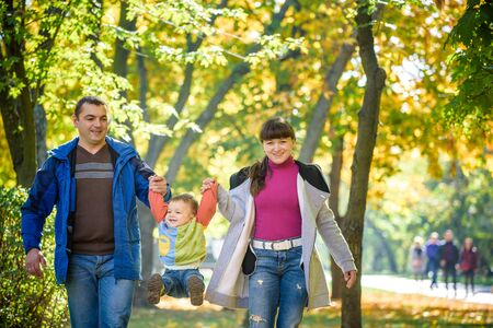 Photo pour Beautiful young family on a walk in autumn forest on maple yellow trees background. Father and mother hold son on hands. Happy family leisure together concept. - image libre de droit
