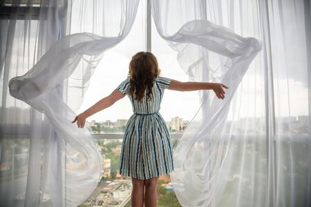 Foto de Rear view of a young joyful woman wearing fashion dress and holding the curtains open to look out of large light window at home, turning to look and smile at camera, interior. - Imagen libre de derechos