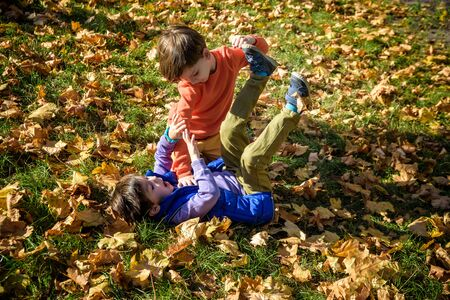 Photo for Two boys fighting outdoors. Friends wrestling in summer park. Siblings rivalry. Aggressive kid hold younger boy on ground, try to hit him. - Royalty Free Image