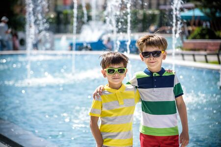 Photo pour Group of happy children playing outdoors near pool or fountain. Kids embrace show thumb up in park during summer vacation. Dressed in colorful t-shirts and shorts with sunglasses. Summer holiday concept. - image libre de droit