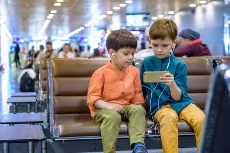 Two little boy sitting in an airport departure hall contentedly playing on his tablet or mobile phone as they wait for his flight with his luggage. Children are laughing and use earphones. Travel with children concept.