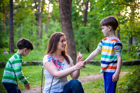 Photo pour Young woman mother applying insect repellent to her two son before forest hike beautiful summer day or evening. Protecting children from biting insects at summer. Active leisure with kids. - image libre de droit