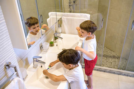 Photo pour Older brother learning to clean the teeth for younger brother in the bathroom with mirror. - image libre de droit