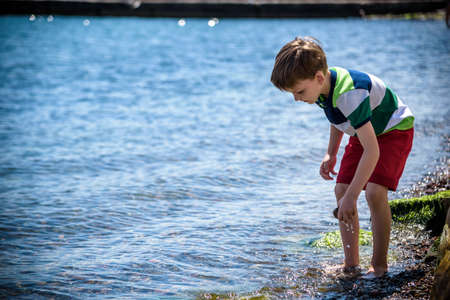 Photo pour The little boy by the sea throws stones in water. Relaxation and vacation with kids. Happy childhood. - image libre de droit