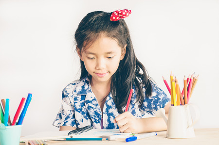 Vintage style photo of a girl is happily coloring a book