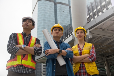 Team of architectures standing at construction site looking at progress.