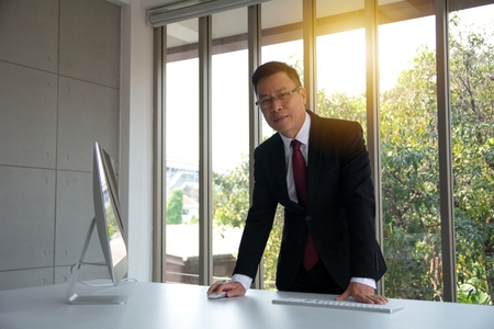 Portrait of confident in formally dressed mature businessman standing in front of a large modern office window