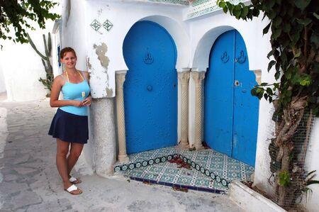 Young attractive female in front of old doors, Hammamet, Tunisia