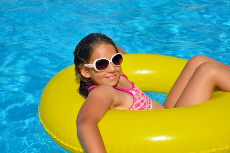 Photo pour Real adorable girl relaxing in swimming pool, summer vacation concept - image libre de droit