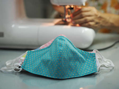 Woman use sew machine to sewing face medical fabric mask protective against during the dust PM 2.5, coronavirus Epidemic, virus covid-19 work Home at home made DIY