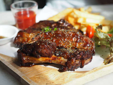 Photo pour Pork Spareribs BBQ, Barbeque Pork Ribs with french fries vegetable salad, tomato sauce in a clear glass on wooden tray, food - image libre de droit