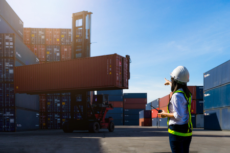 Photo pour Woman Foreman control loading Containers box from Cargo freight ship for import export. - image libre de droit