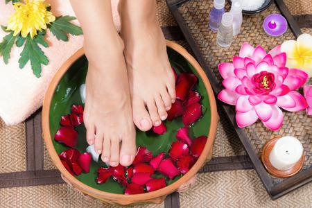 Foto de Closeup shot of a woman feet dipped in water with petals in a wooden bowl. Beautiful female feet at spa salon on pedicure procedure. - Imagen libre de derechos