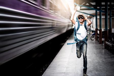 Foto de Traveler man running after a moving train from a railway station - Imagen libre de derechos