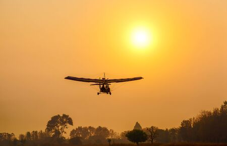Photo pour Ultralight trike flying with a pilot and a passenger against sunset sky, A microlight aircraft with two passengers with the sun - image libre de droit