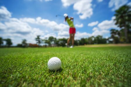 Photo pour Golf girl player hitting ball on professional golf course.   - image libre de droit