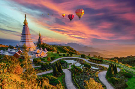 Photo pour Colorful hot air balloons flying over two pagoda in Doi Inthanon Mountain in Chiang Mai, Thailand, Hot air balloon above high mountain at sunset - image libre de droit