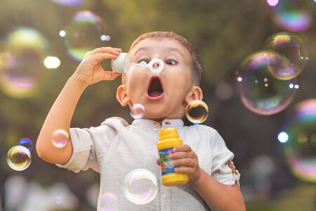 Photo pour A child with an open mouth and big eyes blows colorful soap bubbles in nature - image libre de droit
