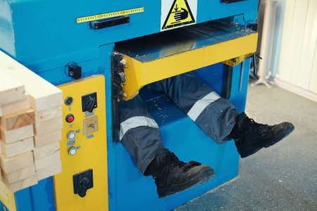 Photo pour The worker has been pulled into the lathe and one leg is sticking out. Staged photo. - image libre de droit