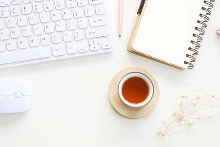 Photo for Red tea and spiral notebook with pencil and mouse and keyboard with dry flower - Royalty Free Image