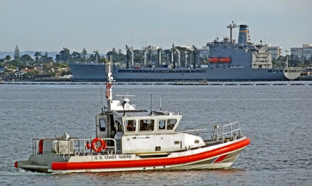 A U.S. Coast Guard RHIB patrols with a naval supply ship in the background.