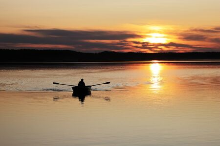 Photo pour Fishing at sunset. Fisherman in boat silhouette at sunset background. - image libre de droit