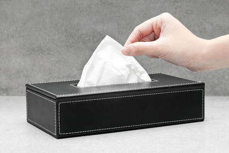 Closeup of a woman hand pulling a facial tissue from a black box tissue