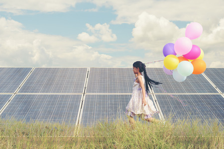 Foto de A funny girl carrying a colorful balloon running in a meadow with a Solar panel, photovoltaic. Concept of Eco-Friendly ,Clean Energy , Pure energy and Sustainable energy - Imagen libre de derechos