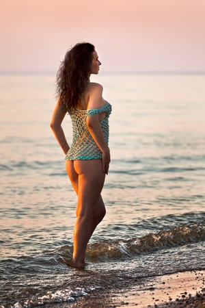 Woman standing at sunset on the seashore