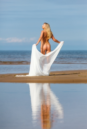 Nude woman on the beach with a white cloth