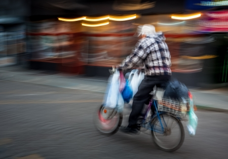 Old man with a large number of packets riding a bicycle around the city. Intentional motion blur