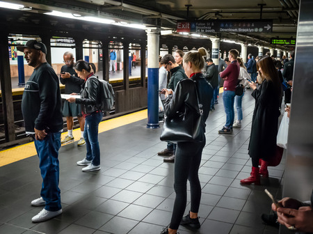 Photo pour New York, USA - Sep 24, 2018: New York and New Yorkers. New York City Subway. Passenger with smartphones waiting for their train - image libre de droit