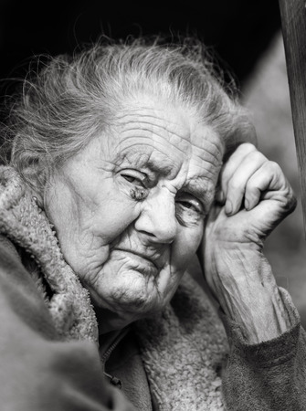 Old age and lifestyle concept. Black and white portrait of a very old and tired wrinkled woman outdoors. Very old hoary woman face closeup portrait. Aging process - very old senior women