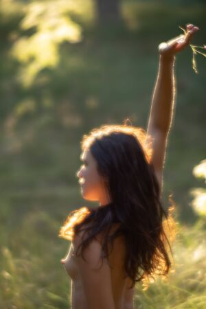 Foto de Soft focus blurred image of a young nude woman in sun light on the forest background. Image in a soft romantic and vintage style - Imagen libre de derechos