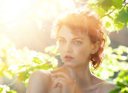 Photo for Portrait of a young red-haired woman among the foliage of trees illuminated by the suns rays - Royalty Free Image